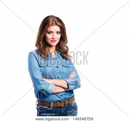 Young beautiful woman in blue denim shirt and jeans, arms crossed, studio shot on white background, isolated