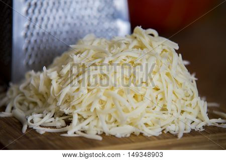 Shredded Mozzarella Cheese On A Cutting Board With A Grater