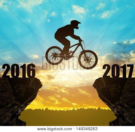 Silhouette cyclist jumping into the New Year 2017 at sunset.
