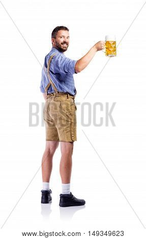 Handsome hipster young man in traditional bavarian clothes holding a mug of beer, rear view. Oktoberfest. Studio shot on white background, isolated.