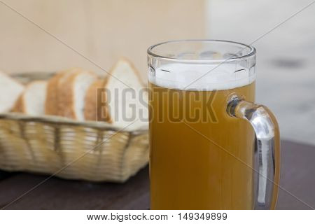 Glass Of Unfiltered Beer And Bread On Wooden Table