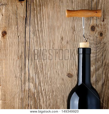 Wine bottle with corkscrew on wooden table
