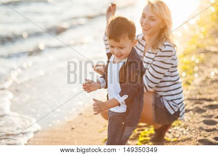 Beautiful boy with a woman relaxing on the beach. Throw pebbles into the sea running jumping laughing and having a great time with each other at sunset.