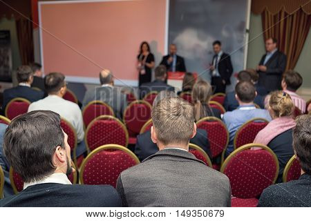 Four Speaker At A Business Conference , And A Rear View Of The Audience