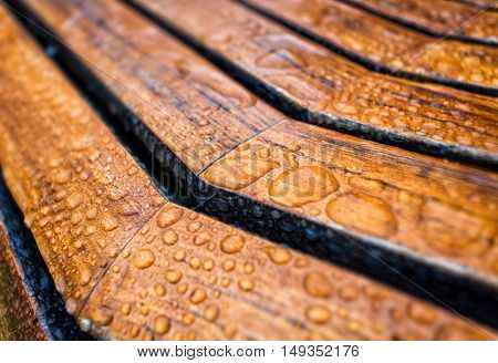 Drops of water on a wooden bench. After rain