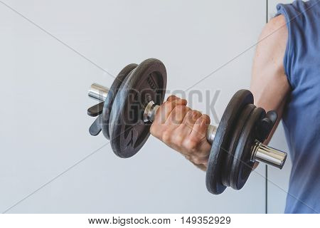 Man lifting weights against a white wall. Space for copy