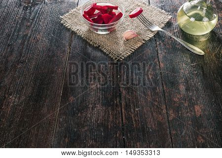 Chopped pickled beets in bowl of dark wooden table