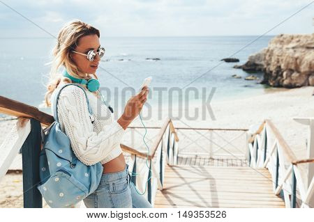 Young woman with backpack wearing sweater and jeans relaxing and listening music at the beach, autumn weekend on the sea shore