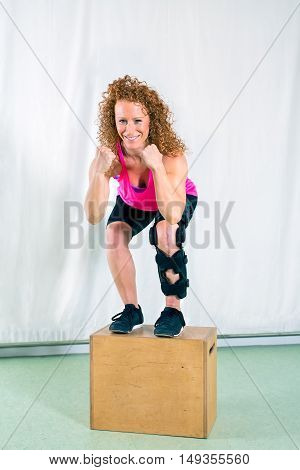 Smiling woman in leg brace stands on wood box near white canvas while wearing bright pink top