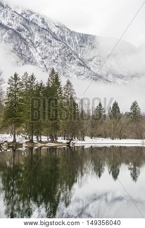 Tranquil winter lake in the mountains with the evergreen conifers reflected in the still water and snowy mountain peaks behind shrouded in wisps of cloud or mist.