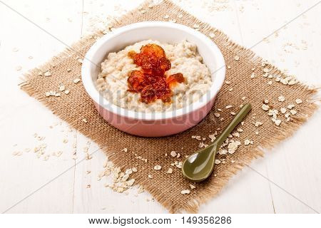 fresh made warm porridge with double cream and orange marmalade in a bowl on jute