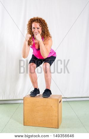Smiling Woman Performing Squats On Box