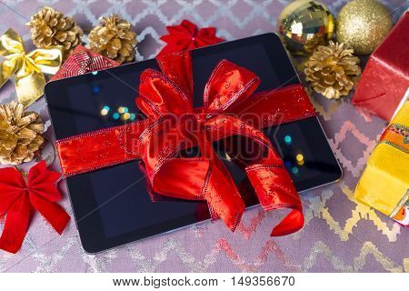 Tablet pc for Christmas with gifts decorations on table.