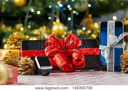 Tablet pc smartphone and smartwatch with gifts and decorations in front of Christmas tree. Focus on smartphone.