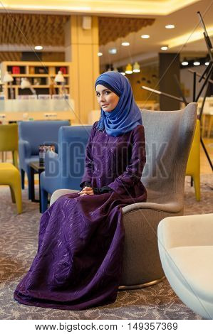 Beautiful muslim woman in modern oriental clothes sitting in a chair in the lobby in a hotel