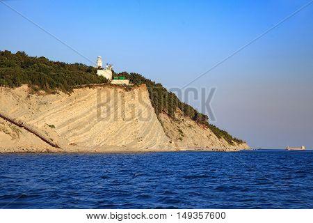 white lighthouse with a blue sky on sea