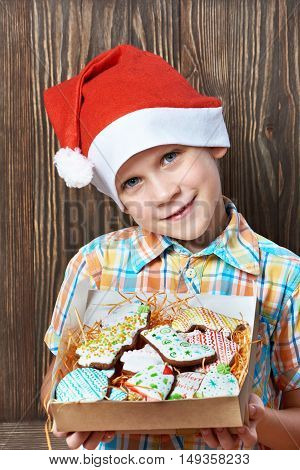 Little Boy In New Year's Red Cap With Box Of Christmas Cookies