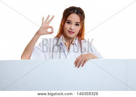 Young Asian Female Doctor Show Ok Sign  Behind Blank White Billboard.