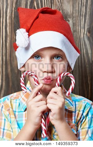 Little Boy In Red Cap With Christmas Lollipops