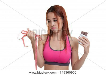 Unhappy Asian Healthy Girl With Chocolate And Measuring Tape.
