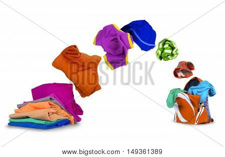 colorful clothing fly out of pile and falls into a backpack isolated on white background