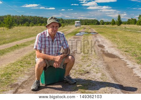 Mature man with old suitcase sitting on an country road in Ukraine