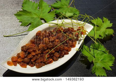 Dry grapes in a white plate with vine leaves