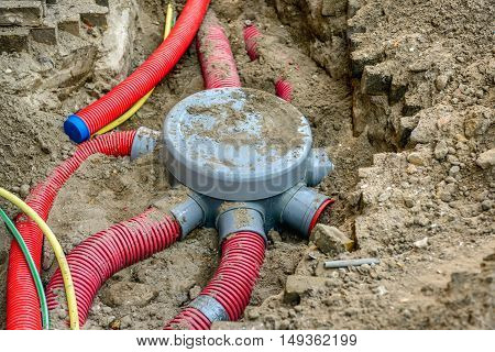 Hole in the ground with a grey covered junction of flexible plastic conduits not yet fastened hoses and cables.