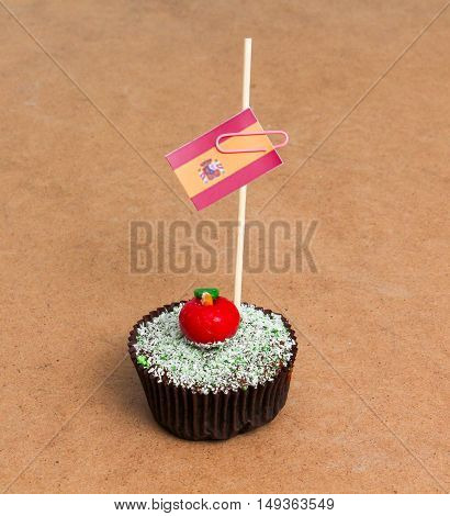 Flag of spain. Apple Cupcake with red apple shape bonbon on the top