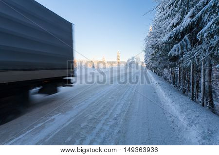 Motion blur of a truck on winter road on frosty day