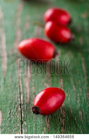Group Of Red Hips Placed On Wooden Board With Green Color