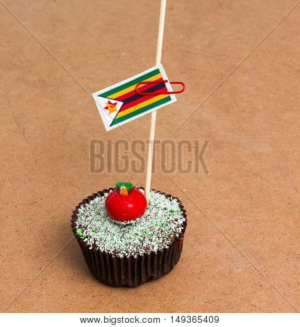 Flag of Zimbabwe. Apple Cupcake with red apple shape bonbon on the top