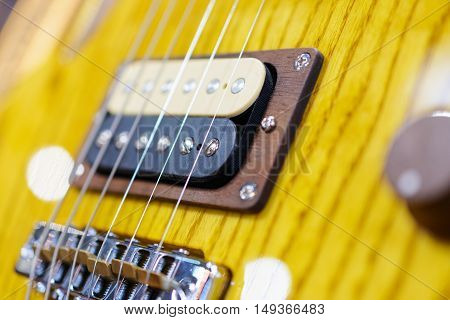 Detail shot of an electric guitar. Visible metal strings and the unit's pickup.