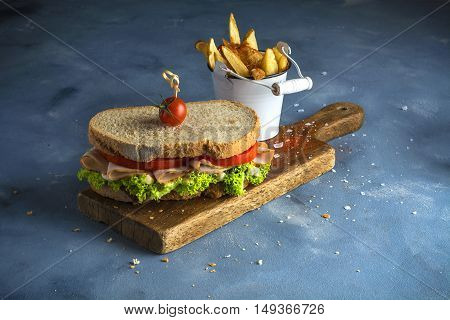 Turkey sandwich with lettuce and tomato and chips.