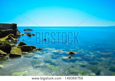 beach of crystalline water with rocks on the left side