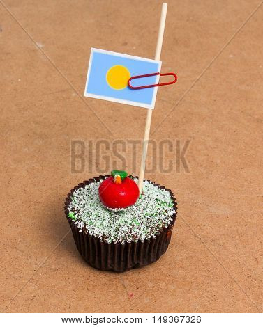 Flag of palau. Apple Cupcake with red apple shape bonbon on the top