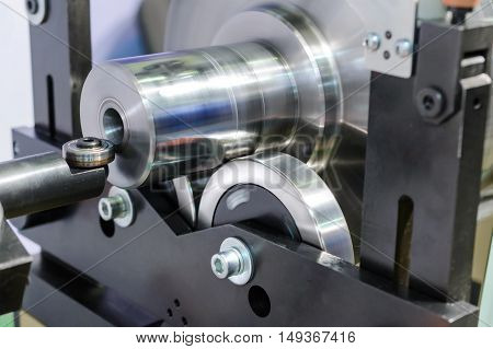 Thick metal shaft mounted on steel wheels. Brilliant, clean surface. Detail of industrial machine for balancing the various parts.