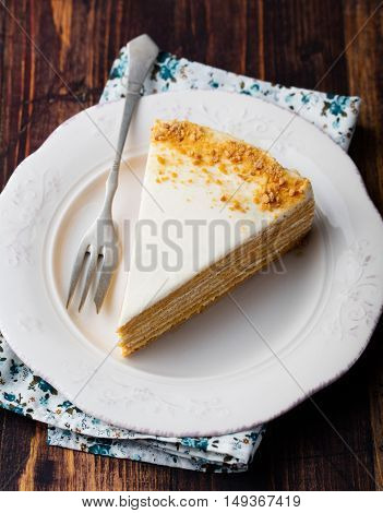 Honey layered cake on a white plate, wooden background.