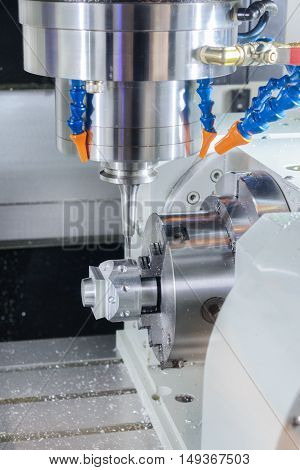 CNC milling machine during operation. Produce drill holes in the metal part.