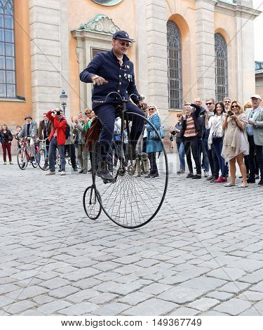 STOCKHOLM - SEPT 24 2016: Man in blue uniform cycling on a high wheeler bicycle in the Bike in Tweed event September 24 2016 in Stockholm Sweden