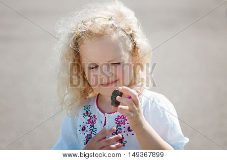 child girl squinted and looks at pebble