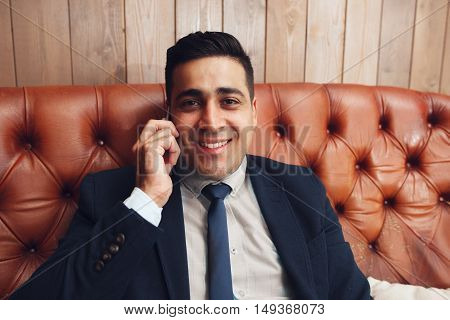 Happy satisfied smiling businessman portrait, free space. Cheerful man with smartphone looking at camera. Positive emotions, happiness, good news concept.