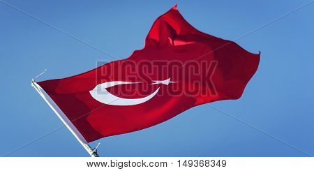 Turkish Flag on the blue sky. Aged photo. Flag of Turkey. Vintage effect. The star and crescent are Muslim symbols. Adrasan Antalya Province Turkey.