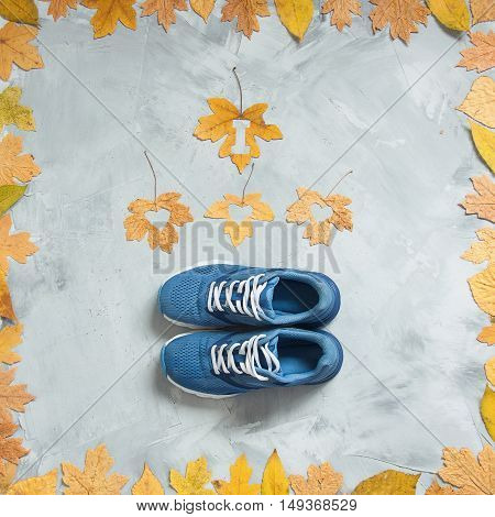 I love running composition with leaves and sport shoes on a concrete background. Concept running in autumn healthy life. Square orientation.