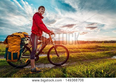 Young woman hiker with loaded bicycle on a green summer meadow at sunset