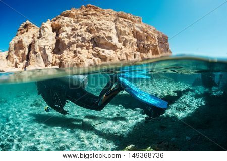 Split shot with diver underwater and rocky land of the Ras Muhammad National Park, Red Sea, Egypt