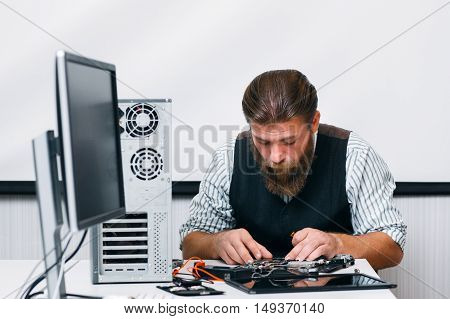 Bearded engineer assembling computer at workplace. Repairman fixing computer inside circuit in office. Electronic renovation, technology, business concept