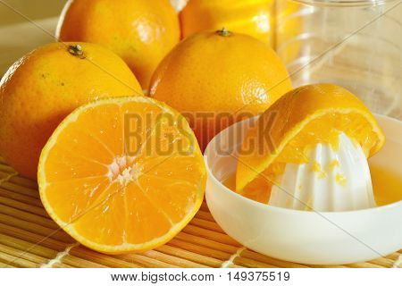 oranges with Reamer juicer on bamboo mat