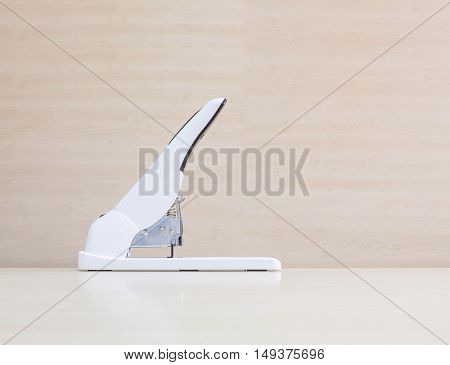 Closeup white stapler office equipment on blurred wood desk and wall in office room textured background under window light