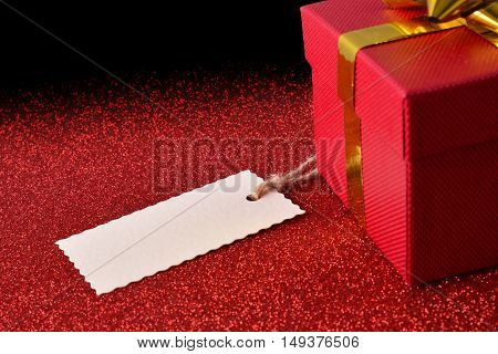 Gift With Tag On Bright Red Textured Table Elevated View